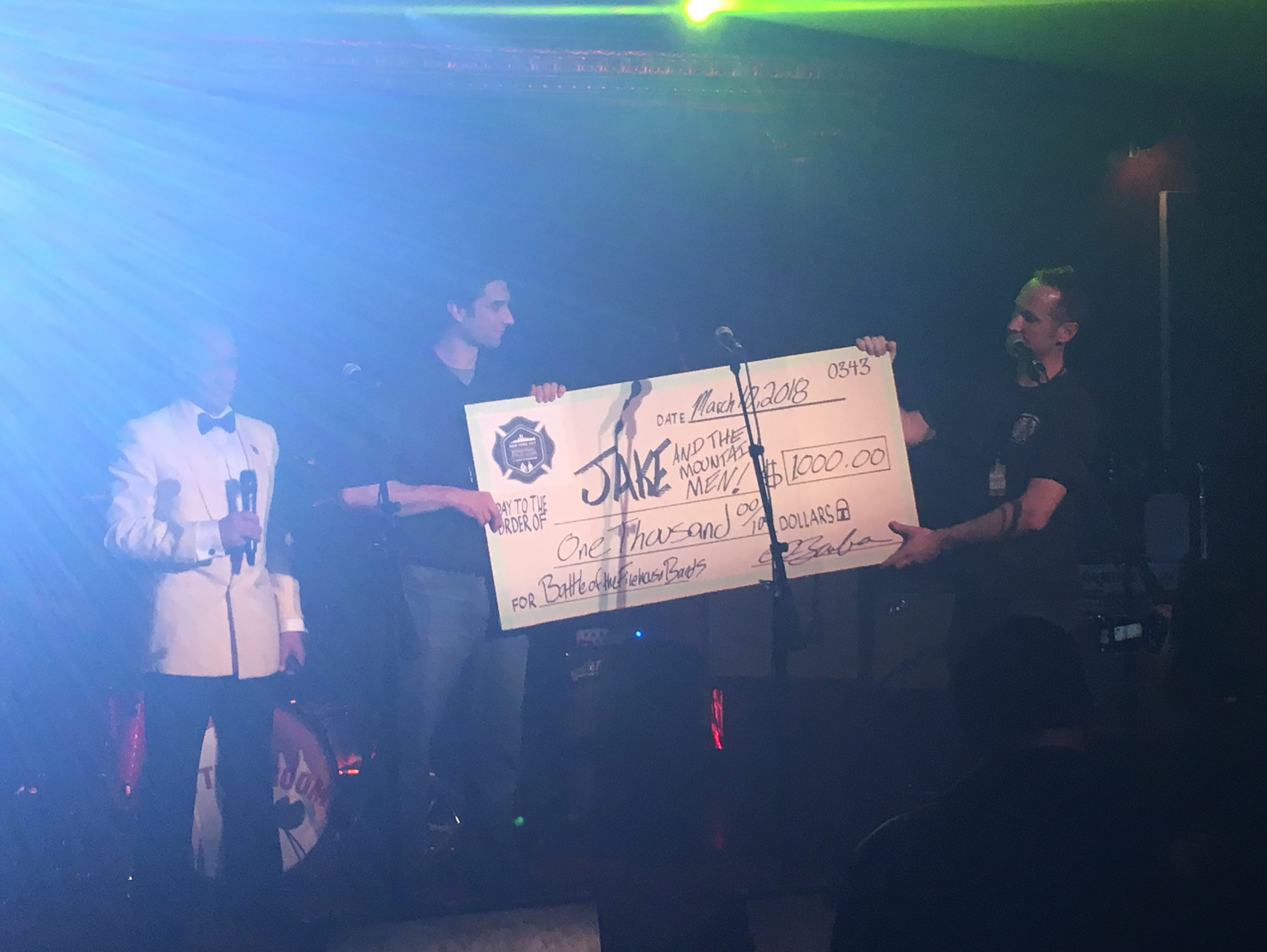 photo of Scott Hickey receiving a check for $1k for winning the Firehouse Battle Of The Bands with Jake And The Mountain Men